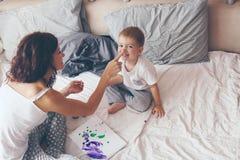Mamá que se relaja con su pequeño hijo Imágenes de archivo libres de regalías