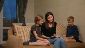 Mamá que se sienta en el sofá con su hija e hijo joven, leyéndolos una historia mientras que se sienta en el sofá en su
