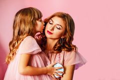 Mamá rubia hermosa con la hija linda en fondo rosado en estudio El día de madre, abrazos mamá de la hija y besos felices imagen de archivo