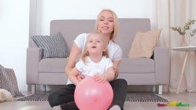 Mamá rubia joven atractiva y su hija encantadora que juegan así como el globo rosado metrajes