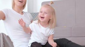 Mamá rubia joven atractiva y su hija encantadora que juegan así como el globo rosado Retrato del primer metrajes
