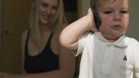 Mamá rubia joven hermosa que juega con su hijo del bebé - meta de los valores familiares - madre y niño caucásicos en casa - almacen de video