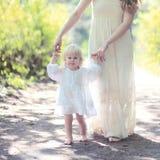 Mamá soleada e hija calientes del retrato que caminan en el bosque fotos de archivo libres de regalías