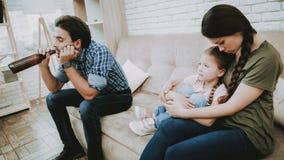 Mamá trastornada con el pequeños niño y padre con alcohol fotos de archivo