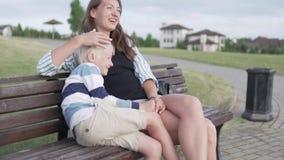 Mamá y abrazo y risa del hijo la familia se sienta en un banco en el parque del verano metrajes