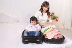 Mamá y bebé con equipaje de la maleta y ropa asiáticos lista fotografía de archivo
