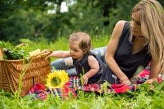 Mamá y bebé en la naturaleza que tiene comida campestre fotografía de archivo