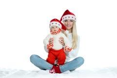 Mamá y bebé lindos en los sombreros de santa fotografía de archivo