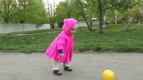 Mamá y bebé que juegan en el parque con la bola metrajes