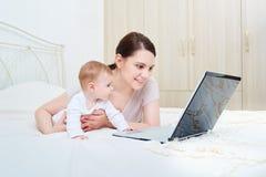 Mamá y bebé que miran un ordenador portátil y una sonrisa felices Imagen de archivo libre de regalías