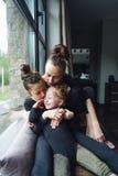Mamá y dos hijas junto en la ventana Fotografía de archivo