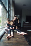 Mamá y dos hijas junto en la ventana Fotografía de archivo libre de regalías