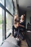 Mamá y dos hijas junto en la ventana Fotos de archivo