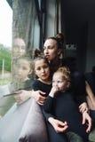 Mamá y dos hijas junto en la ventana Fotos de archivo libres de regalías