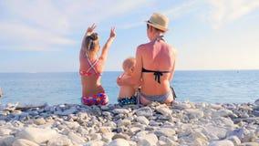 Mamá y dos niños jovenes que se sientan en la playa y que miran el mar metrajes