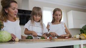 Mamá y dos que sus hijas cocinan en la cocina: la muchacha de las adolescencias corta los chiles de las pimientas rojas y su pequ almacen de video