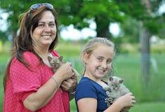 Mamá y hija sonriente alegre y nuevos gatitos del animal doméstico Imagenes de archivo