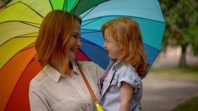 Mamá y muchacha debajo del paraguas coloreado en naturaleza almacen de video