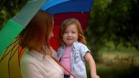 Mamá y muchacha debajo del paraguas coloreado en naturaleza almacen de metraje de vídeo