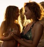Mamá y muchacha en puesta del sol Foto de archivo libre de regalías