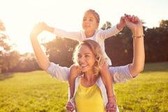 Mamá y niño femenino en sus hombros fotos de archivo libres de regalías
