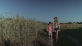 Mamá y niño que caminan en el camino rural en campo metrajes