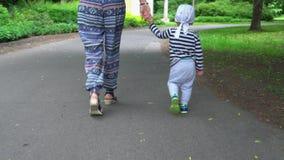 Mamá y niño que llevan a cabo las manos que caminan junto en la carretera de asfalto El cardán sigue almacen de metraje de vídeo