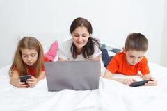 Mamá y niños con smartphones Fotografía de archivo libre de regalías