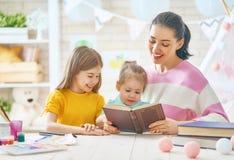 Mamá y niños que leen un libro foto de archivo