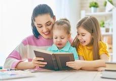 Mamá y niños que leen un libro fotografía de archivo libre de regalías