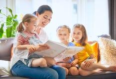 Mamá y niños que leen un libro fotos de archivo