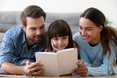 Mamá y papá con poco libro de lectura lindo de la hija junto fotos de archivo