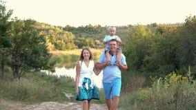 Mamá y papá con un hijo joven en su cuello que camina cerca del río en el parque en la puesta del sol en un día de verano, hablan almacen de video