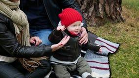 Mamá y papá e hijo que se sientan en una manta almacen de video