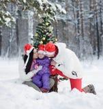 Mamá y papá que besan a la hija cerca de un árbol de navidad en bosque del invierno foto de archivo libre de regalías