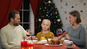 Mamá y papá que besan a la hija en el almuerzo de la Navidad, mirando a la cámara, víspera del día de fiesta almacen de metraje de vídeo