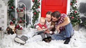 Mamá y papá que leen un libro a su hijo que se sienta comfortablemente en la nieve almacen de metraje de vídeo