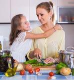 Mamá y pequeña hija que cocinan el plato vegeterian dentro Foto de archivo libre de regalías