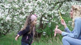 Mam? y peque?a hija que juegan con las burbujas de jab?n en jard?n floreciente, c?mara lenta metrajes