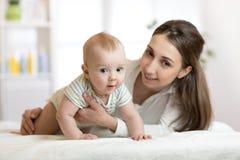 Mamá y pequeño hijo en cama Bebé infantil de abarcamiento de la madre Foto de archivo