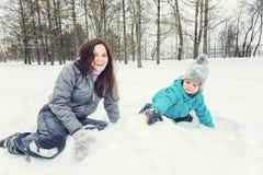 Mamá y pequeño hijo que juegan en la nieve fotos de archivo