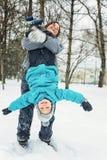 Mamá y pequeño hijo que juegan en la nieve foto de archivo