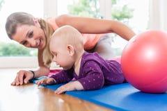 Mamá y su bebé que practican para arrastrarse en curso de la madre y del niño fotografía de archivo