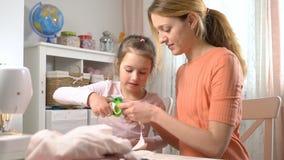 Mamá y su pequeña hija hacer la costura junta La muchacha con las tijeras corta el paño para DIY metrajes