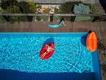 Mamá y su resto de la hija en la piscina imágenes de archivo libres de regalías