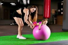 A mamã é contratada com sua filha no gym com uma bola da aptidão imagens de stock
