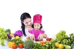 Filha da mostra da mãe para cortar o vegetal Fotografia de Stock