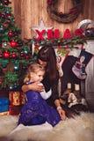 A mamã abraça a filha na pele branca perto da chaminé fotografia de stock royalty free