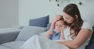 A mamã abraça seus dois poucos filhos no sofá na sala de visitas e olha a tevê Família que presta atenção à tevê