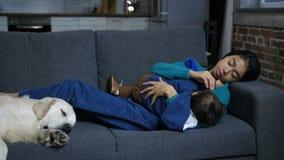 Mamã afetuosa que amamenta o menino infantil no sofá filme